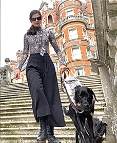 Aria Mia Loberti and her black Lab guide dog Ingrid descend the stairs at Royal Holloway University