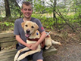 Ethan sits on a bench hugging his yellow Lab guide dog Ginsburg