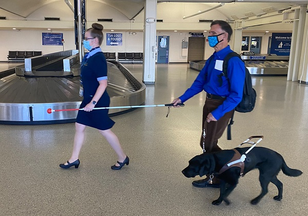 An airline employee assists a man with a guide dog in an airport luggage area