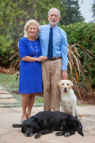 GDB donors John and Erika Ammirati in their backyard with their career change dogs Fondy, a yellow Lab, and Shiloh, a black Lab.