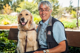 Bruce and his golden retriever guide dog Marley sit on a park bench