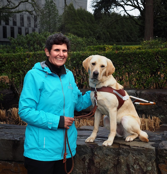 Chari Chauvin stands while her guide dog Haviland sits on a rock wall by her side