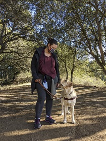 GDB graduate Ginny Prince standing on a wooded path looking at her yellow lab guide dog Biscuit
