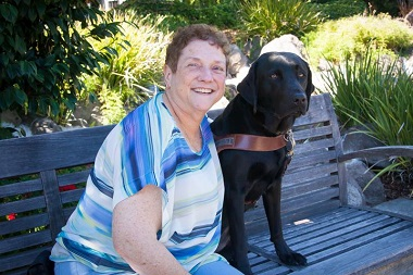 Dorianne sits on a garden bench next to her black Lab guide dog, Dime.