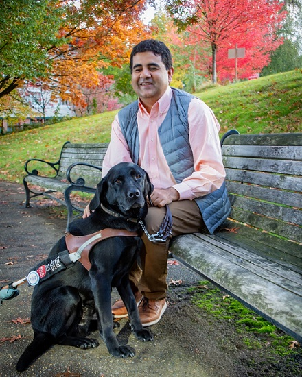 Amit is seated on a bench with his black Lab guide dog, Tashi. Behind the team is a grassy hill and trees full of fall colored leaves.