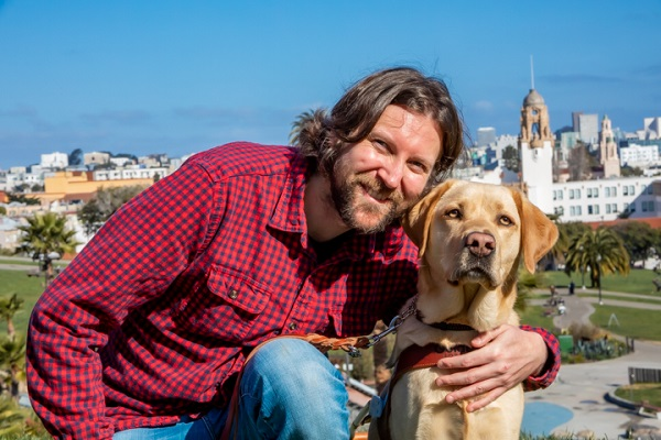 Graham Norwood and his guide dog, Malcolm, in front of the San Francisco city skyline