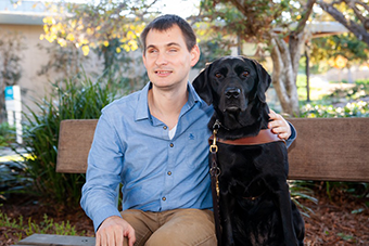 Jake is seated on a bench beside his black Lab guide dog, Forli.