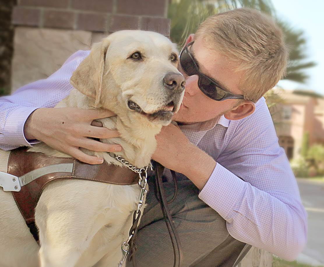 GDB Grad, Jake Olson, embraces his yellow Lab guide dog, Quebec.