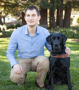 Jake Koch and his black Labrador Retriever guide dog pose for a photo on the grass.