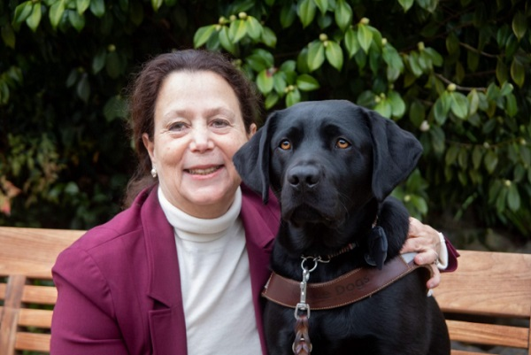 GDB Grad Janni Lehrer-Stein sits on a bench with her arm around her black Lab guide dog, Shiloh.