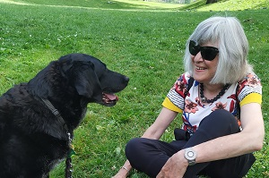 Joan and her black Lab Tallulah sitting on the grass