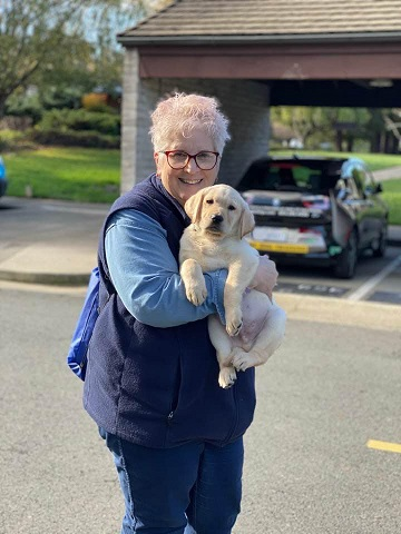 Marybeth holds yellow Lab puppy Barley in her arms outside our kennel on our California campus. A carport is behind them.