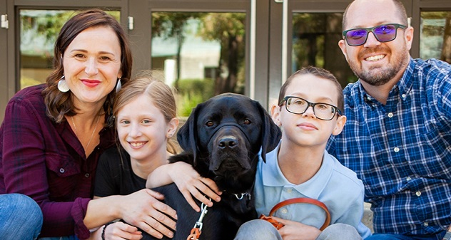 A family of four poses with their black Lab, a K9 Buddy.
