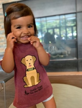 A young girl wearing a GDB logo t-shirt with a graphic design of a Golden Retriever on it smiles at the camera.