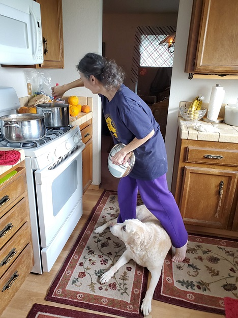 Mary Ann stirs a pot on her stove while a yellow Lab foster dog lounges between her legs on the kitchen rug.