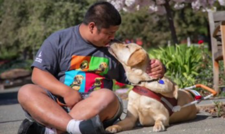 Kevin gets a kiss from his yellow Lab guide dog Fender
