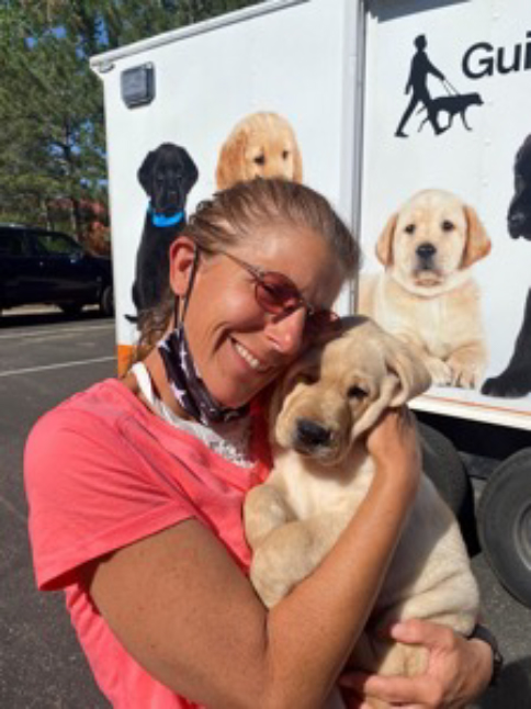 Puppy raiser Wendy Davis smiles as she holds a yellow Lab puppy