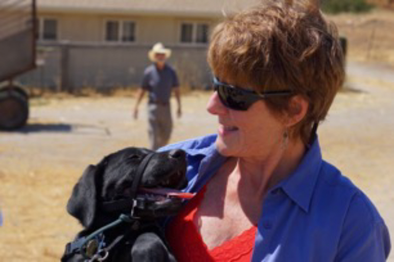 Tami gazes down at a black Lab puppy in her arms